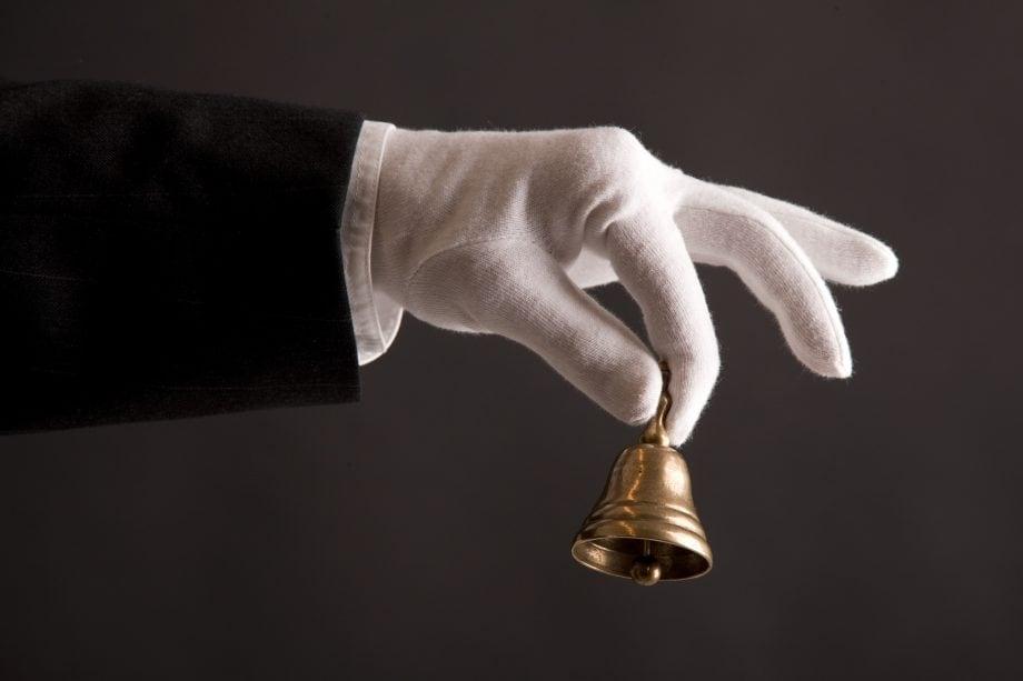 Hand schüttelt eine Glocke