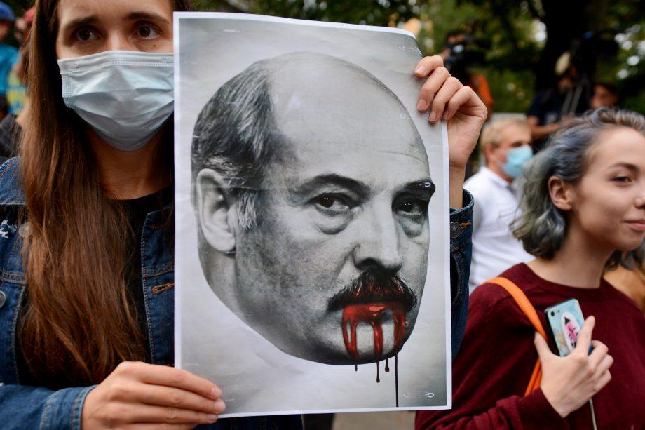 Demonstrantin hält Bild von Lukaschenko hoch
