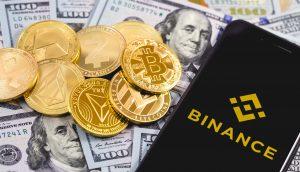 Krypto-Münzen liegen auf US-Dollar-Noten. Daneben liegt ein Smartphone mit Binance-Logo