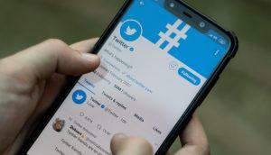 Frau hält Handy mit geöffneter Twitter-Seite in der Hand