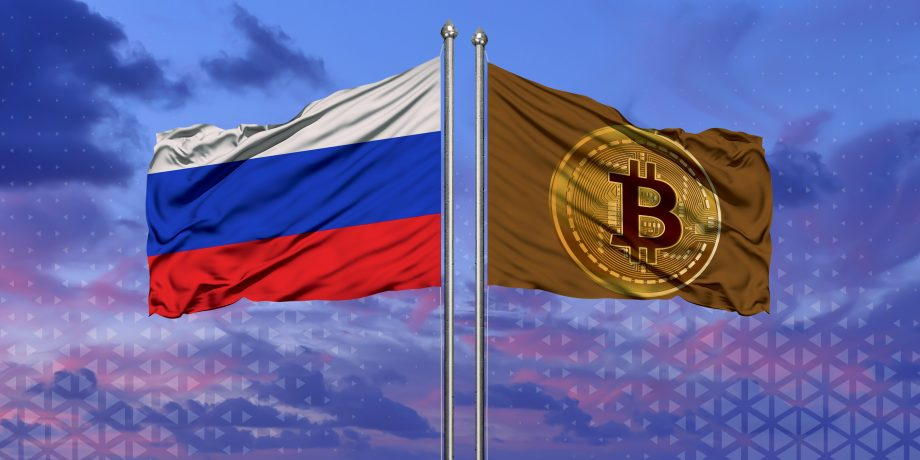 Russische Flagge weht neben Bitcoin Flagge