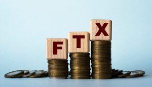 FTX-Buchstaben-Würfel liegen auf Geldmünzen-Haufen