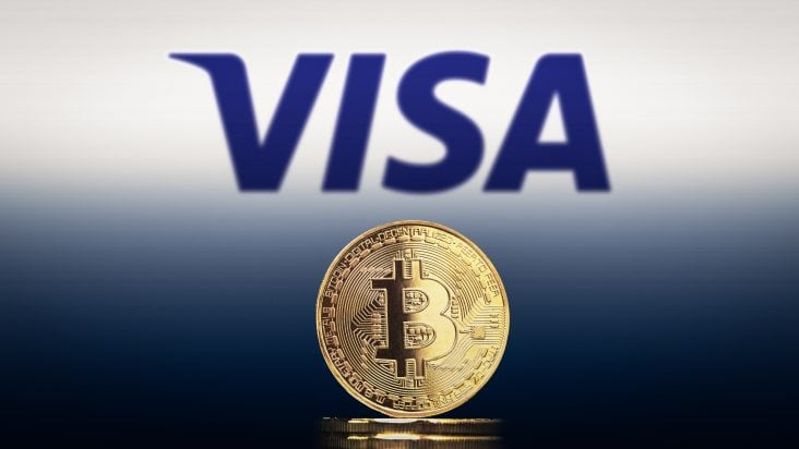 Visa Logo im Hintergrund und Bitcoin Münze steht davor