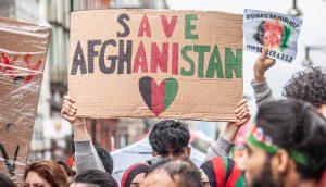 Save Afghanistan in schwarz, rot, grün geschrieben auf einem Pappschild wird in mitten einer Menschenmenge hoch gehalten