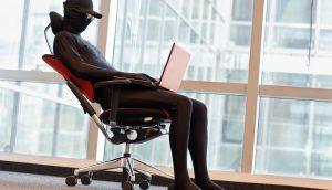 maskierte Person in zurücklehnender Haltung auf einem Bürostuhl