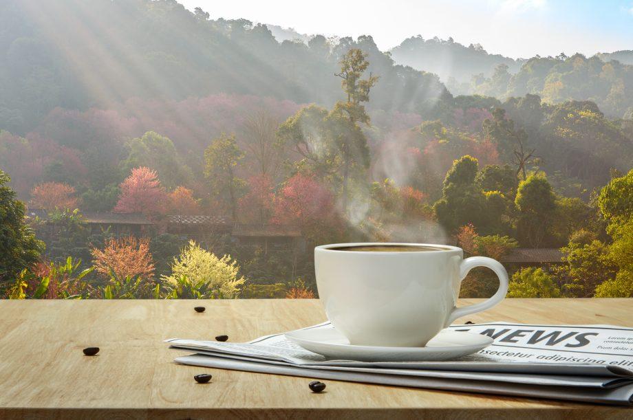 Kaffee und Nachrichten liegen auf Tisch