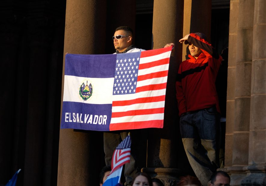 Mann hält zwei geteilte Flagge vor Regierungsgebäude