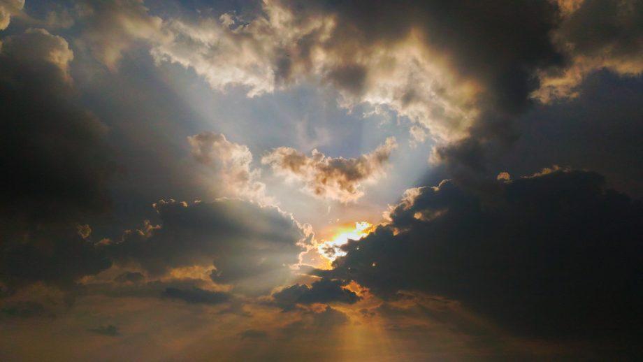 Grau-Orange-gefärbter Himmel mit durchschimmernden Sonnenstrahlen