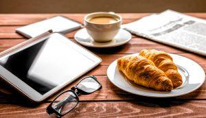 Kaffeetasse, Tablet, Brille, zwei Croissants, Handy und eine Zeitung auf einem Holztsich.