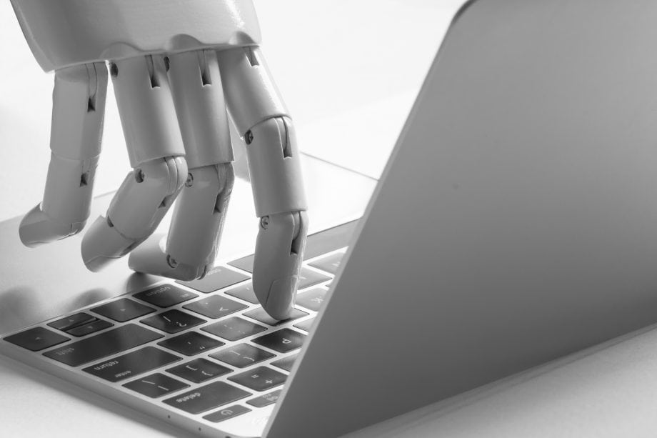 Eine Roboter Hand tippt auf einem Laptop