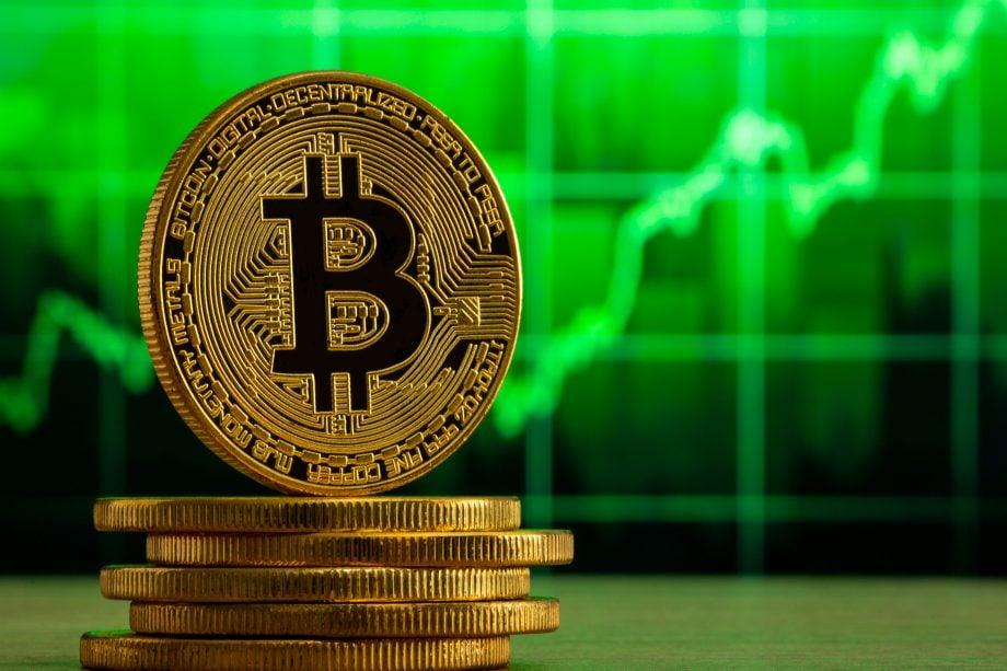 Bitcoin-Münze vor grünem Chart