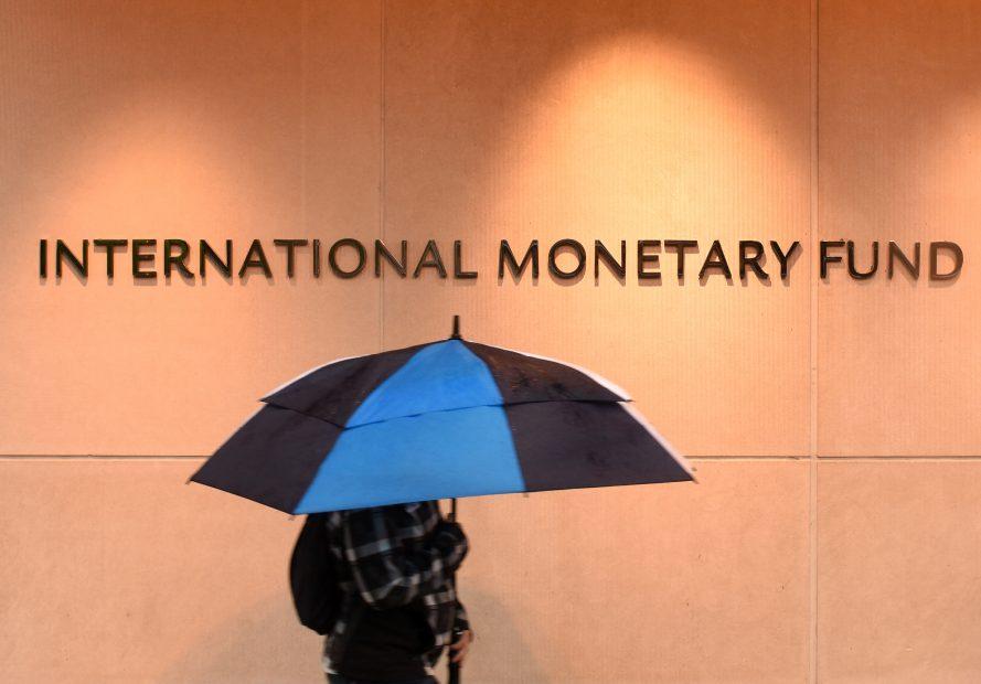 Logo des Internationalen Währungsfonds auf einer Betonwand. Davor ein Mensch mit blauem Regenschrim.