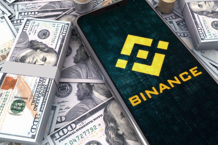 Geldbündel auf denen ein mobiles Endgerät liegt, dass auf der Seite von Binance ist