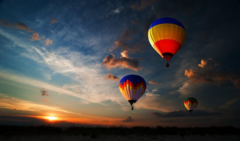 Mehrere Heißluftballons steigen in den Abendhimmel.