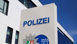 Bild des Polizei Schilds mit NRW Flagge darunter.