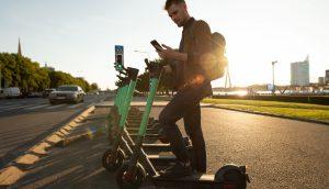 junger Mann mit Roller und Telefon