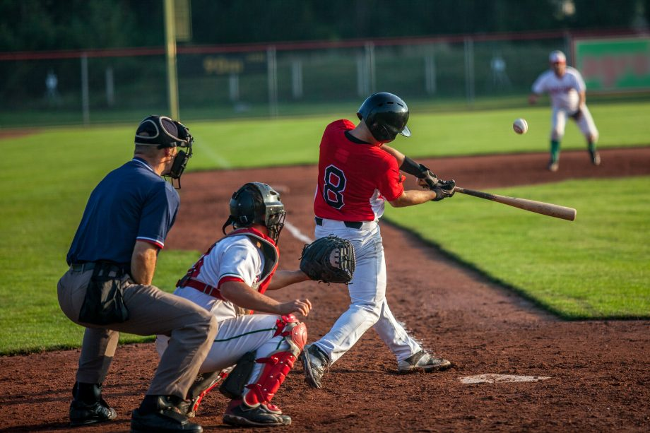 Baseballspieler schlägt Ball