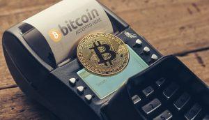 Bitcoin-Münze liegt auf Kreditkartenlesegerät